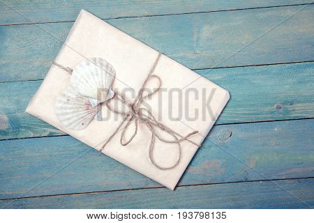 Paper wrapped package with two sea shells on white wooden background