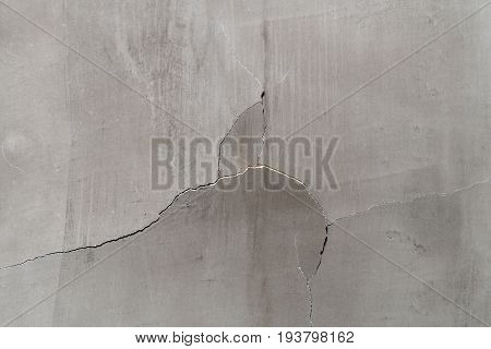 Fissured surfaces thin crack, Deep break in a light yellow concrete cement wall texture background
