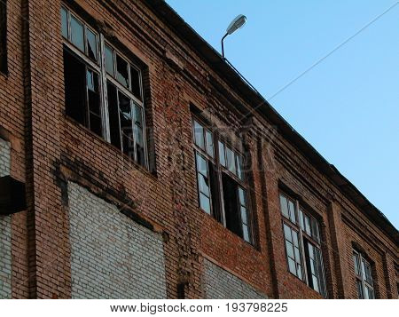 The broken windows of the building on blue sky background.