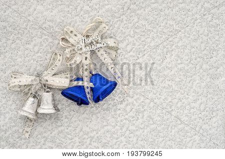 christmas bells with bows and merry christmas text on a silver brocade background with copy space
