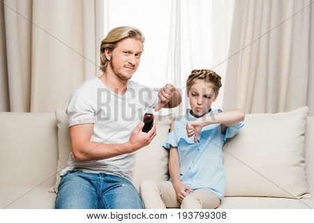 dissatisfied daughter and father holding syrup and showing thumbs down at home