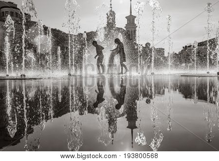 KIEV UKRAINE - Jun 28 2017: Happy children playing in a water fountain and enjoying the cool streams of water in a hot day