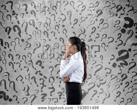Side view of confused businesswoman with question marks on wall