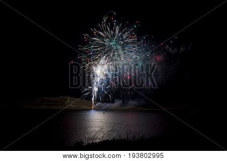 Colorful fireworks display over water to celebrate Fourth of July Independence Day at Lake Isabella California