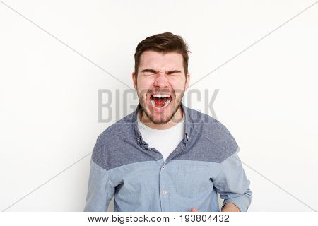 Portrait of angry crying man, isolated. Aggressive guy with closed eyes screaming loudly, white background. Psychotherapy exercise