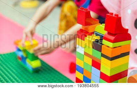 Preschooler child playing with colorful toy blocks. Preschool children build tower with plastic block. Toddler kid in nursery.