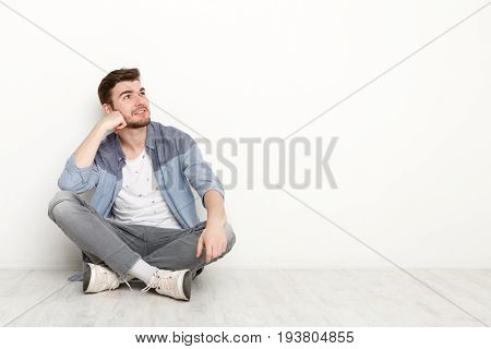 Pensive young man sitting on floor and looking upwards. Handsome relaxed guy dreaming about something, lost in thoughts, isolated on white background