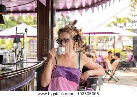 Senior woman drinking coffe in pool bar. Tropical Bali island.