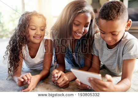 Happy African-American children lying and browsing tablet on floor together.