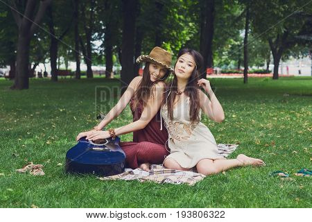 Fancy girls have picnic in park on grass. Modern hippie boho style