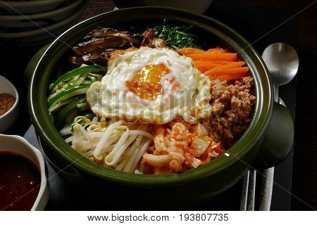 close up bibimbap, traditional korean food ,mixed rice served in a bowl rice topping alot kind of vegetable ,meat or pork, and fried egg