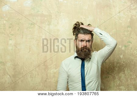 bearded man or hipster with long beard and raised hand on stylish hair on serious face in tie and white shirt on textured beige background copy space
