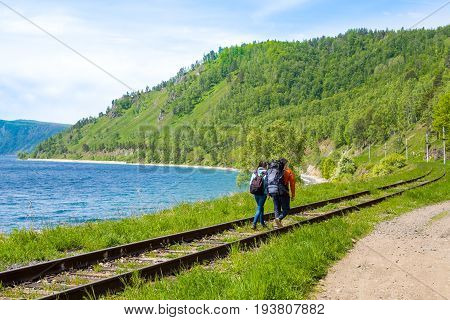 A pair of backpackers go along the Circum-Baikal railway. Lake Baikal, Siberia, Russia