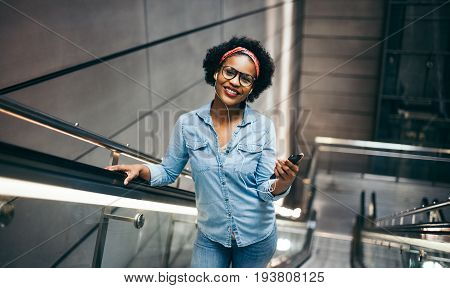 Smiling Young Woman Riding Up An Escalator Listening To Music