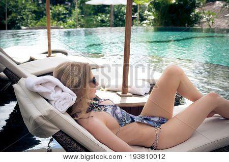 Sexy Beautiful woman sunbathing in swimming pool.