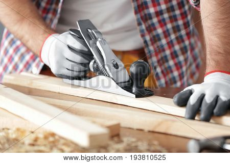 Carpenter planing wooden plank on table, closeup