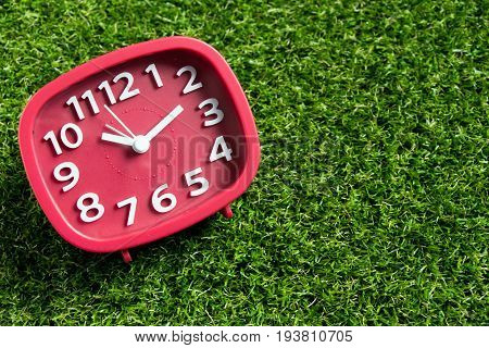 Red analog clock on artificial green grass background