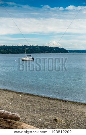 Two boats are anchored in the Puget Sound with Mount Rainier in the distance.