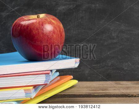 Apple on the top of notebooks near chalkboard