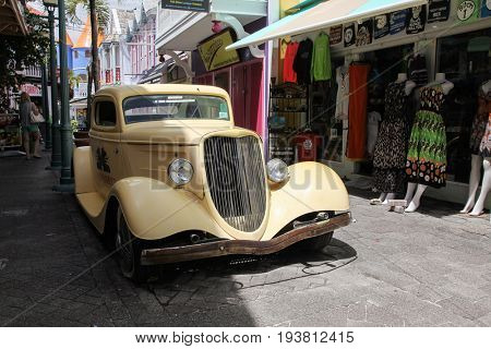 PHILIPSBURG - AUGUST 2:  Old Street with antique car near Great Bay walkway with restaurants and gift stores in Philipsburg, seen in St.Maarten on August 2, 2015