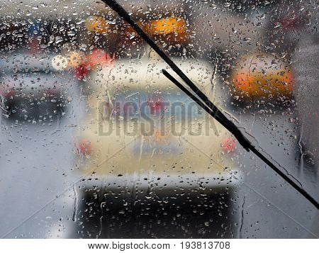 A trip by car in the rain around the city. From the window through the raindrops you can see the highway