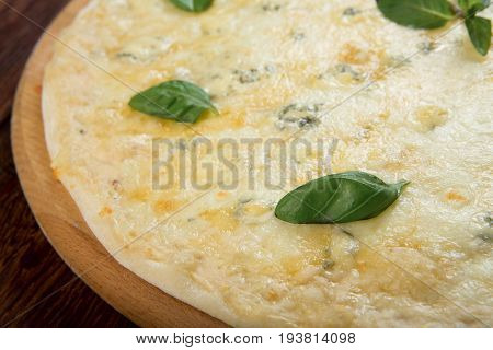 Delicious Quaddro formaggi, four cheese pizza on wood background, with parmesan, cheddar, mozzarella and blue cheese decorated with basil leaves