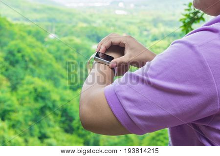 Hand Of Fat Asian Woman Use Bracelet Smart Watch Over The Mountain In Tropical Forest Nature
