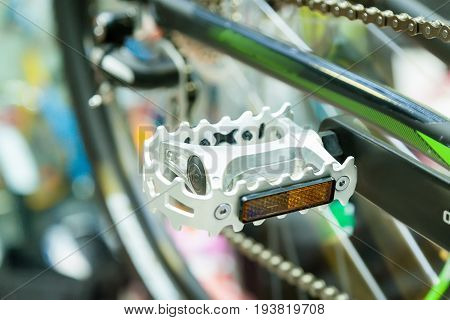Bicycle silvery color pedal on a blurred bicycle background