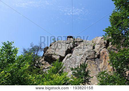 Girl rock climber climbs on the rock