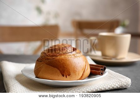 Yummy cinnamon roll with cup of tea on kitchen table