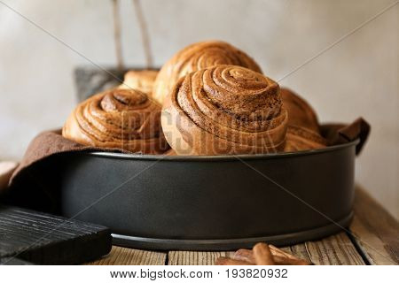 Cake pan with yummy cinnamon rolls on wooden table
