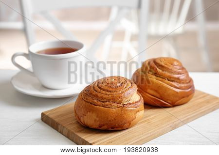 Wooden board with yummy cinnamon rolls and cup of tea on white table