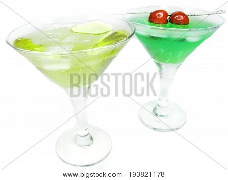 two alcohol green liqueur cocktails with ice and cherry