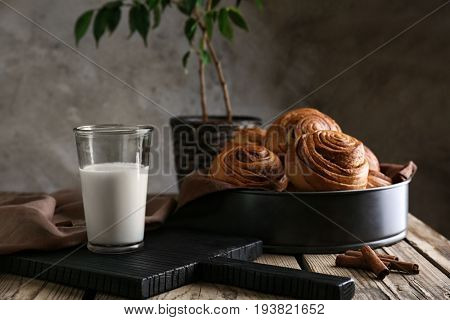 Cake pan with yummy cinnamon rolls and glass of milk on wooden table