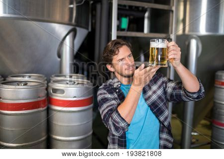 Worker examining beer in glass at brewery