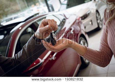 Close up of salesman giving car keys to female customer while standing in showroom