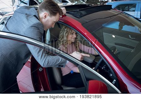 Salesman guiding female customer sitting in car at showroom
