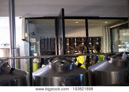 Workers examining pressure gauge at brewery seen through glass
