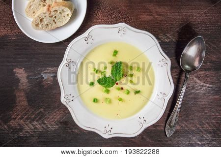 Overhead photo of vichyssoise, French potato and leeks soup, with chopped green onions, pink peppercorns, and mint leaves, on dark rustic texture with bread, spoon, and place for text
