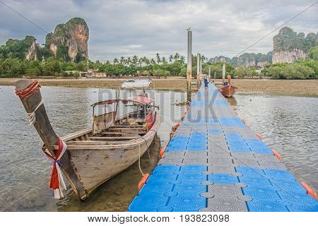 Traditional long tail boat on Railay Beach with walkway to harbor and view of green island, Krabi Provine, Thailand. (HDR filter effect)