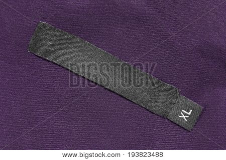 Clothes label lettered XL on purple cotton as a background