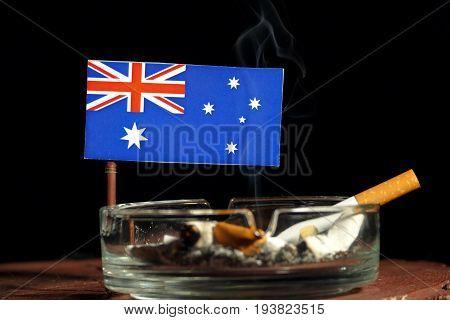 Australian Flag With Burning Cigarette In Ashtray Isolated On Black Background
