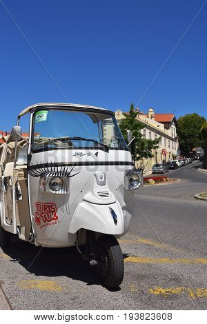 Sintra Portugal - June 6 2017: Funny tuk tuk with eyelashes on car lights on the street of Sintra in Portugal very popular transport among tourists