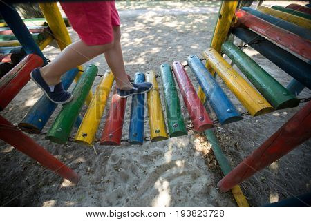 Low section of boy walking on jungle gym at playground