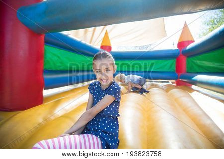 Portrait of happy girl sitting on bouncy castle while brother playing in background