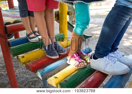 Low section of friends walking on jungle gym at play ground
