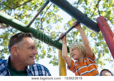 Low angle view of father and son looking at each other while playing on jungle gym