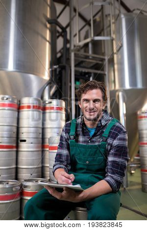 Portrait of smiling worker with clipboard sitting on keg at warehouse