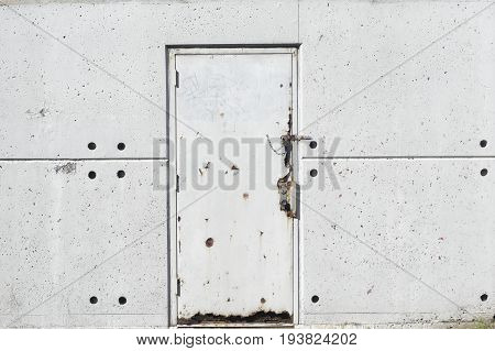 A textured white metal door on a concrete wall. Outside at a train station.