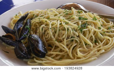 Spaghetti seafood with mussels and fresh green onions. Seafood Pasta with cooked mussels in shell, served on a white dish with spoon.